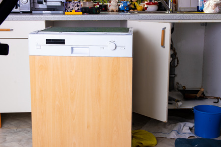 People in technician jobs. A broken built-in dishwasher in a white kitchen was removed from the kitchenette.
