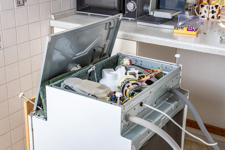 People in technician jobs. A broken built-in dishwasher in a white kitchen was removed from the kitchenette then turned upside down and the bottom cover opened.