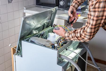 Menschen in Technikerberufen. Gerätereparaturtechniker oder Heimwerker arbeitet an einer kaputten Spülmaschine in einer Küche. Arbeiter wechselt das Heizelement.