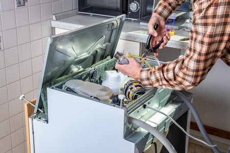 Personas en trabajos de técnico. El técnico de reparación de electrodomésticos o el personal de mantenimiento trabaja en un lavavajillas roto en una cocina. Obrero está cambiando el elemento calefactor.