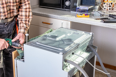People in technician jobs. A broken built-in dishwasher in a white kitchen was removed from the kitchenette then turned upside down and the bottom cover will be opened now.
