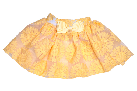 Girls clothes. Festive beautiful yellow little girl short summer skirt with floral pattern and a golden ribbon bow isolated on a white background. Children and kids fashion.