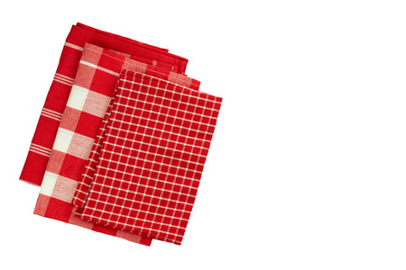 Stack of red white checkered and striped linen tableclothes. Isolated on white background.