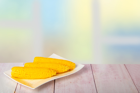 Ripe fresh corn fruits on rustic wooden table in front of abstract blurred spring background. For your food and product display montage. Concept healthy food. Reklamní fotografie