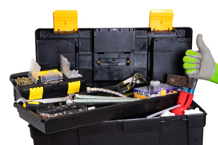 Tool box isolated. Black plastic tool kit box with assorted tools and a glove showing the thumb up sign for good work isolated on a white background.