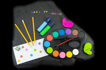 Closeup of colorful school supplies with copy space on blackboard background. Back to school written with colorful letters on blackboard. Concept education.