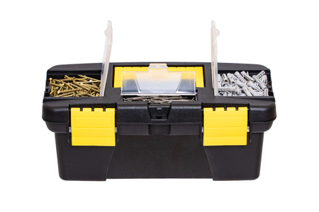 Tool boxes isolated. Closeup of a little black plastic tool kit box with yellow handle and clasp and with nails, screws and dowels isolated on a white background. Macro.