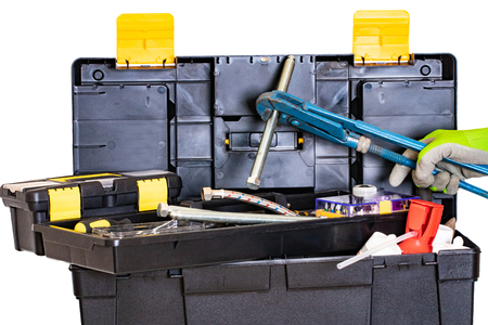 Boîte à outils de plombier ou de menuisier isolée. Boîte à outils en plastique noir avec des outils assortis et une main avec un gant tenant une grosse vis avec une grosse clé à pipe. Isolé sur fond blanc.