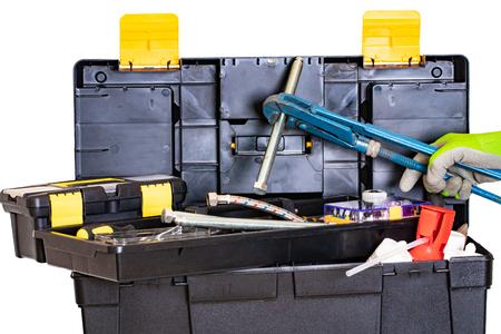 Caja de herramientas de fontanero o carpintero aislada. Caja de juego de herramientas de plástico negro con una variedad de herramientas y una mano con guante que sostiene un tornillo grande con una llave de tubo grande. Aislado en un fondo blanco.