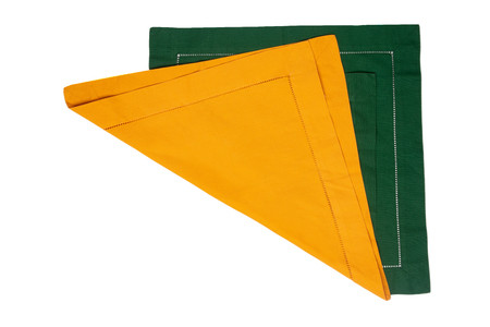 Closeup of a green and a yellow napkin or tablecloth isolated on white background. Kitchen accessories.