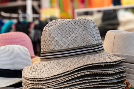 Straw hats background. Closeup with selective focus on a stack straw hats for sale with blurred market shop background. Macro.