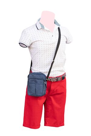 Male mannequins. Closeup of male mannequin dressed in white cotton shirt and red short pants and a blue bag, isolated on a white background. Mens summer fashion. Macro. Stock Photo
