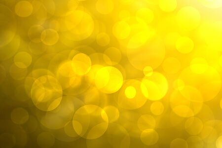 A festive abstract golden yellow gradient background texture with glitter defocused sparkle bokeh circles. Card concept for Happy New Year, party,  invitation, valentine or other holidays.