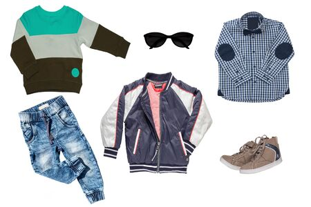 Collage set of children clothes. Denim jeans or pants, a pair shoes , a rain jacket, shirt and a sweater for child boy isolated on a white background. Concept spring autumn and summer clothes.