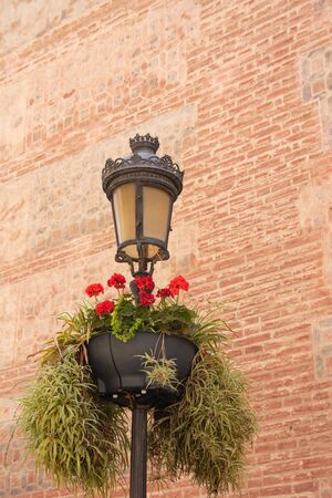 A lamp post decorated with red flowers in front of old brick facade in centre of malaga. MALAGA, SPAIN, Andalusia May 28, 2019.