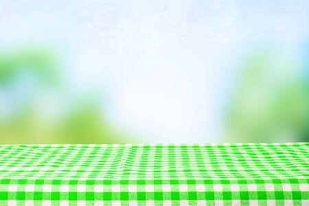 Table de bureau en bois vide avec nappe à carreaux vert sur fond bleu clair abstrait vert printemps ou été. Modèle pour votre montage d'affichage de nourriture et de produit.