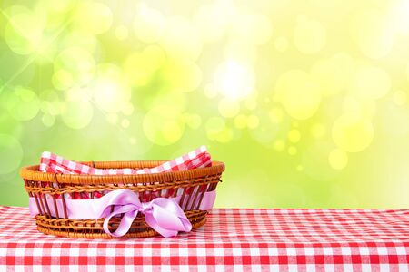 Empty basket with purple ribbon on red checkered tablecloth with abstract bright yellow spring or summer background. For your food and product display montage.