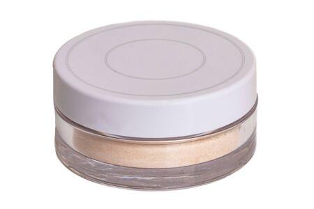 Polvo facial aislado. Primer plano de un polvo suelto translúcido para la cara en un frasco cerrado aislado sobre fondo blanco. Belleza del concepto.