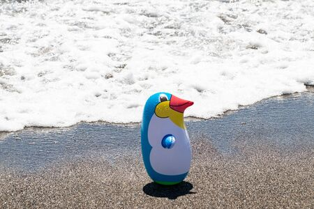 Beach toy background. Selective focus on one colorful inflatable rubber penguin toy at a sandy sunny beach. Space for advertising. Macro.
