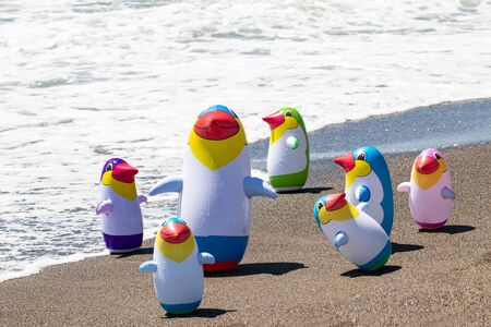 Beach toy background. Selective focus on a group of seven colorful inflatable rubber penguin toys at a sandy sunny beach. Space for advertising. Macro. Stockfoto