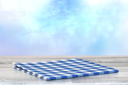 Empty table top summer background. Closeup of a empty blue checkered tablecloth or napkin on a rustic bright gray table over abstract blue sky. Template for food and product display montage.