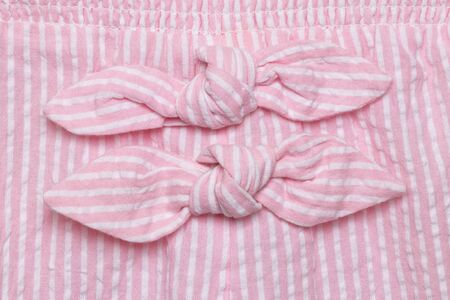 Bow on dress. Close-up details of two decoration ties at pink white striped summer dress of little girl. Macro.