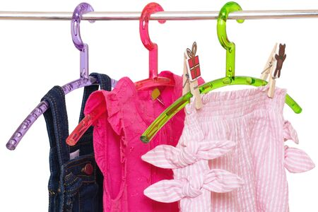 Girls clothes on rack. Close-up of colorful stylish summer dresses and a short pants for the little girl on a rack isolated on a white background. Clothes for kids on hanger. Macro. Imagens