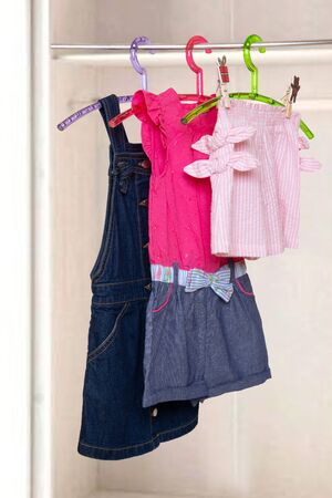 Girls clothes on rack. Collage of colorful stylish summer dresses and a short pants for the little girl on a rack in a blurred wardrobe background . Clothes for kids on hanger.
