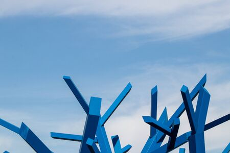 Selective focus on a detail of a blue abstract wooden construct against blue cloudy sky at a sunny autumn day. Macro. Imagens