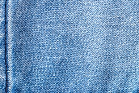 Denim background texture. Close-up of details of empty light blue jeans fabric jean surface with dark blue vertical seam on left side.  Macro. Top view. Beautiful backdrop with space. Stock fotó