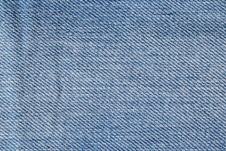 Denim background texture. Close-up of details of empty light blue jeans fabric jean surface. Macro. Top view. Beautiful backdrop. Stock fotó