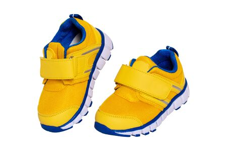 Child shoe fashion. Close-up of a pair of yellow blue child sneaker or sport shoes isolated on a white background. Elegant and trendy shoes for girls. Macro.