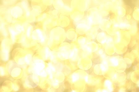 A festive abstract delicate golden yellow gradient background texture with glitter defocused sparkle bokeh circles. Card concept for Happy New Year, party invitation, valentine or other holidays.