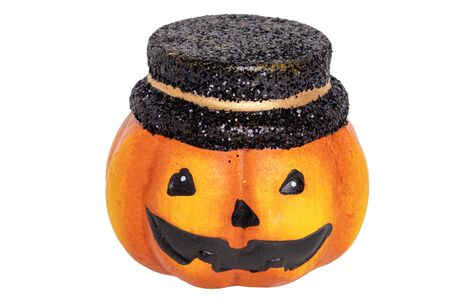 Halloween pumpkin isolated. Close-up of a decoration Halloween pumpkin with black hat made of ceramics isolated on a white background. Macro. Imagens