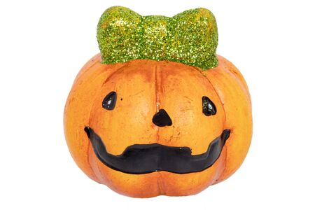 Halloween background isolated. Close-up of a funny decoration Halloween pumpkin with a green hair bow made of ceramics isolated on a white background. Macro. Stock Photo
