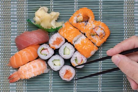 Traditional japanese sushi menu. Closeup of male fingers which with the help of chopsticks pick up a sushi roll from a complete sushi menu.  There are sushi rolls with salmon, sashimi and other slices of raw fish. Stock fotó