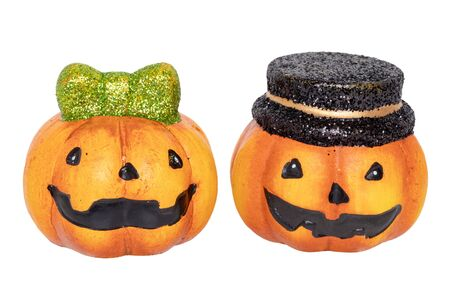 Halloween pumpkin isolated. Close-up of two decorations Halloween pumpkins one with black hat and other with a green hair bow made of ceramics isolated on a white background. Macro.