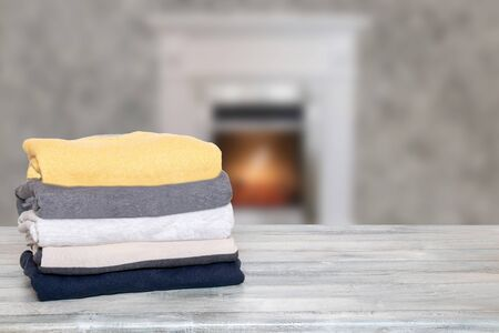Stack of winter clothes. Pile of colorful knitted cozy warm cashmere sweaters or pullover on wooden table against abstract blurred Interior fireplace background. Space for display product montage.