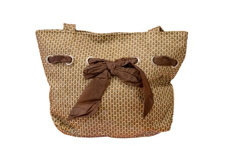 Beach bag. Close-up of a light brown beach bag with a brown bow ribbon isolated on a white background. Concept travel. Stock Photo