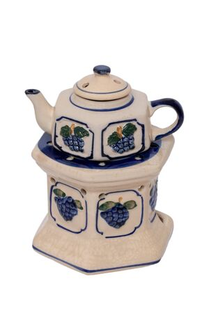 Close-up of a vintage teapot with warmer made of ceramic pottery  with a colorful blue pattern isolated on a white background. The tea on the stove is kept warm with a tealight. Macro.
