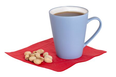 Coffee cup background isolated. Close-up of a blue coffee mug and pistachios on a red napkin isolated on a white background. Concept morning coffee. Macro. Archivio Fotografico - 133516269