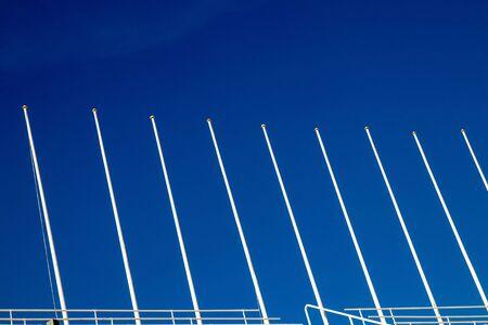 Flag poles against blue sky. Image of nine white big and empty flagpoles against blue sky with selective focus. Shot made in Olympic Stadium Barcelona, Spain. Archivio Fotografico - 133516271