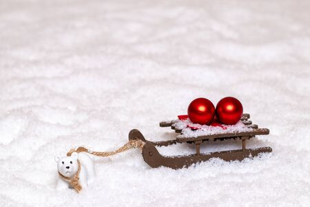 Christmas greeting card template. A little polar bear pulls a sleigh with two red Christmas balls through the snow. Copy space for your design. Macro photograph.