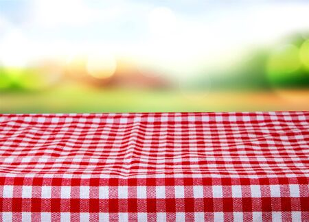 Empty wooden desk table with red checkered tablecloth over abstract bright light green spring or summer background. Template for your food and product display montage.