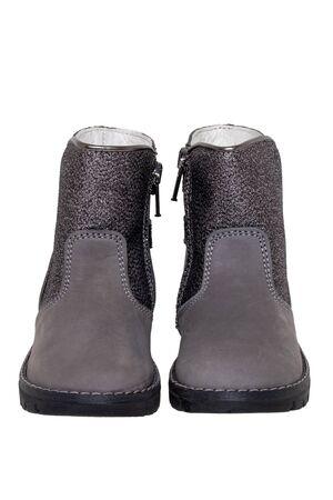 Botas de invierno. Primer plano de un par de elegantes botas de invierno de cuero gris plateado forradas con cuero blanco. Nuevas tendencias de moda de zapatos de invierno para niñas aisladas sobre fondo blanco. Fotografía macro.