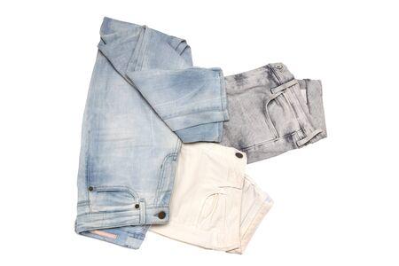 Moda de jeans. Primer plano de la colección de tres mujeres varios pantalones de mezclilla o pantalones vaqueros coloridos aislados sobre un fondo blanco. Vista superior plana laical.