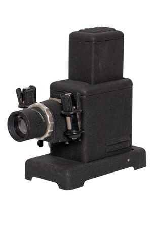 Vintage projector. Close-up of a old black projector for viewing slides and filmstripes isolated on a white background. Entertainment last century to look holiday pictures on a projection screen. Macro.