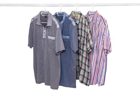 Hanging shirts isolated. Closeup of collection of four male various colorful t-shirts on a clothes rail isolated on a white background. Mens summer fashion.