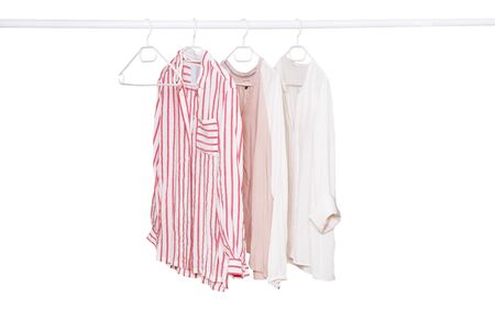 Hanging blouses isolated. Closeup of collection of three female various colorful blouses on a clothes rail isolated on a white background. Womens summer fashion.