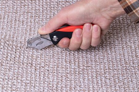 People in handyman jobs. The hand of a craftsman cuts a carpet with a professional tool for laying flooring work. Macro photograph.